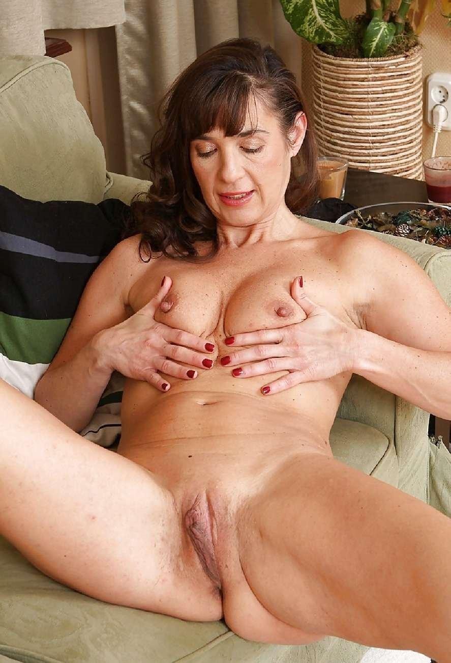 фото голой зрелой женщины за 50 сидящей на диване и сжимающей сиськи руками, видна бритая пизда.
