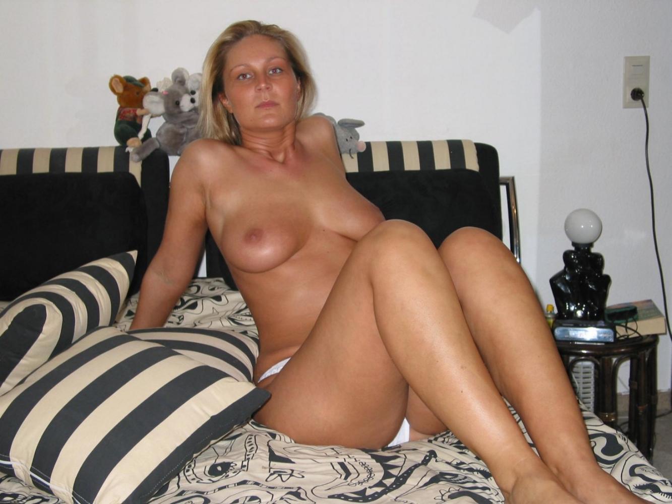 фото голой зрелой женщины с красивыми сиськами торчком сидящей на диване.