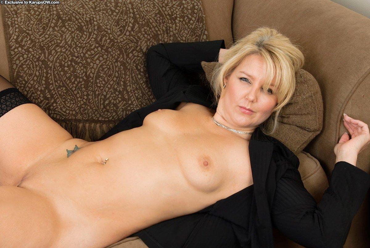 фото голой зрелой женщины красивая блондинка лежит на диване оголив грудь, в пупке пирсинг