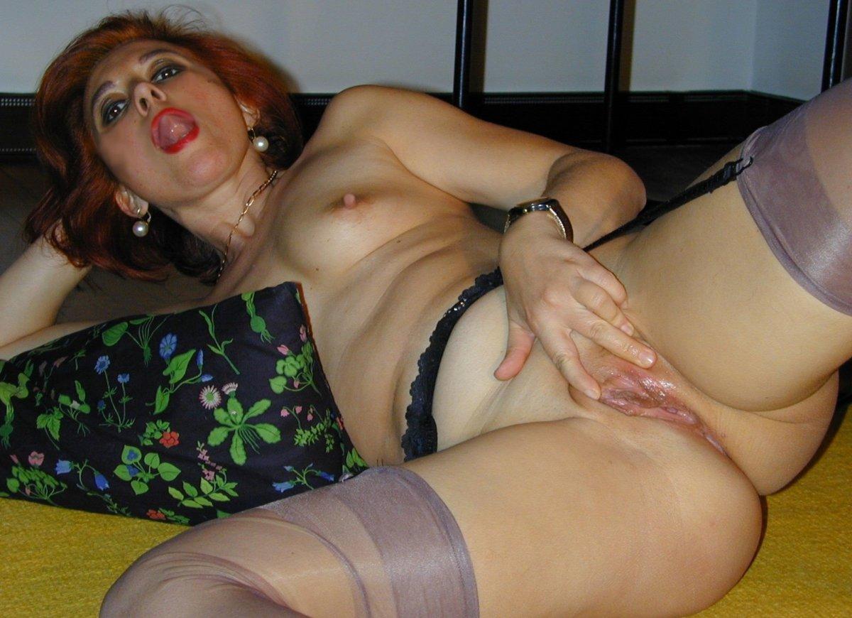 фото голой зрелой женщины лежит на кровати раздвинув ноги и расширяя пальцами пизду и открыв рот подняла язык готовая отсосать.