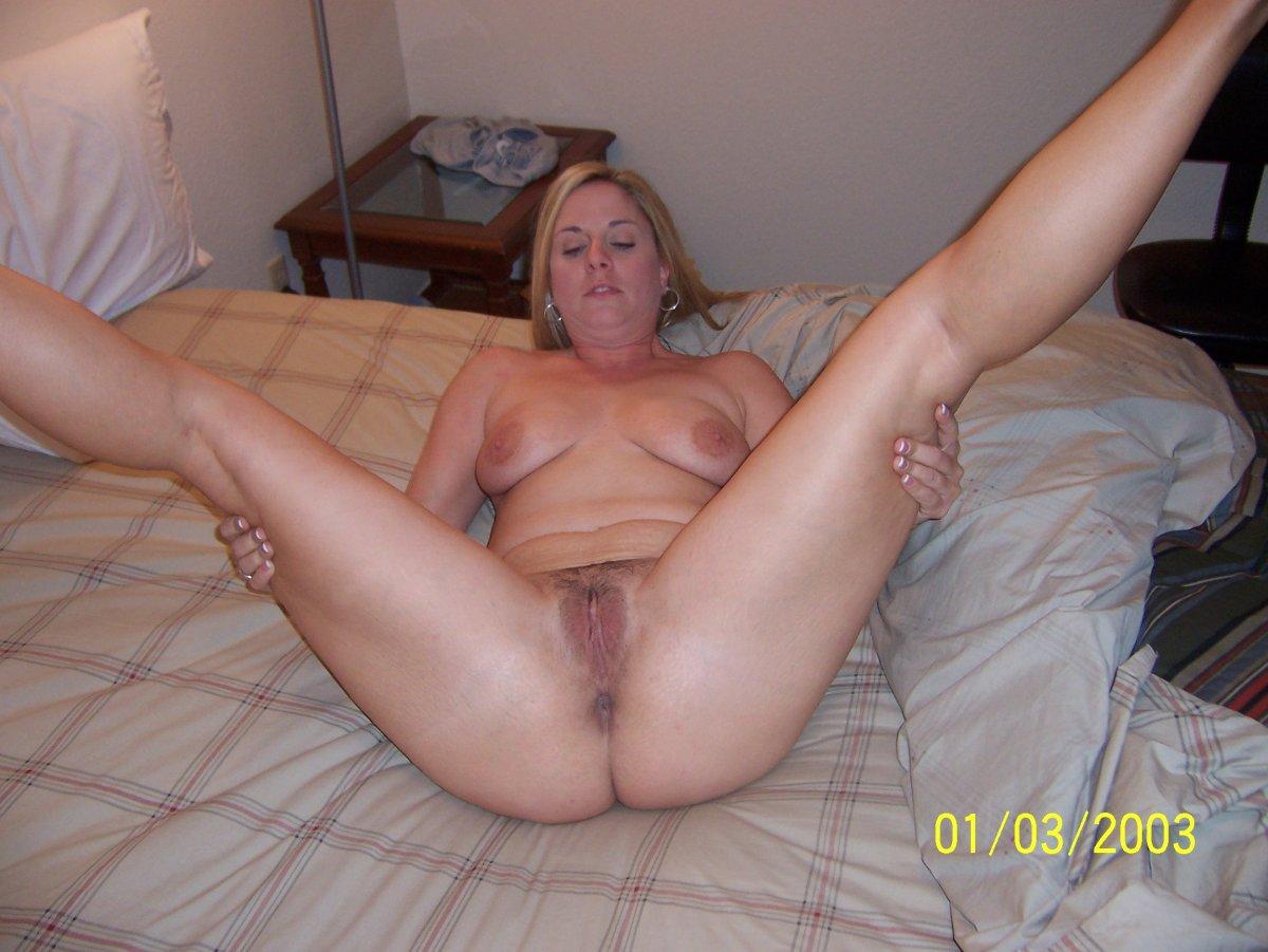 фото голой зрелой женщины лежит на кровати подняв и широко раздвинув ноги.