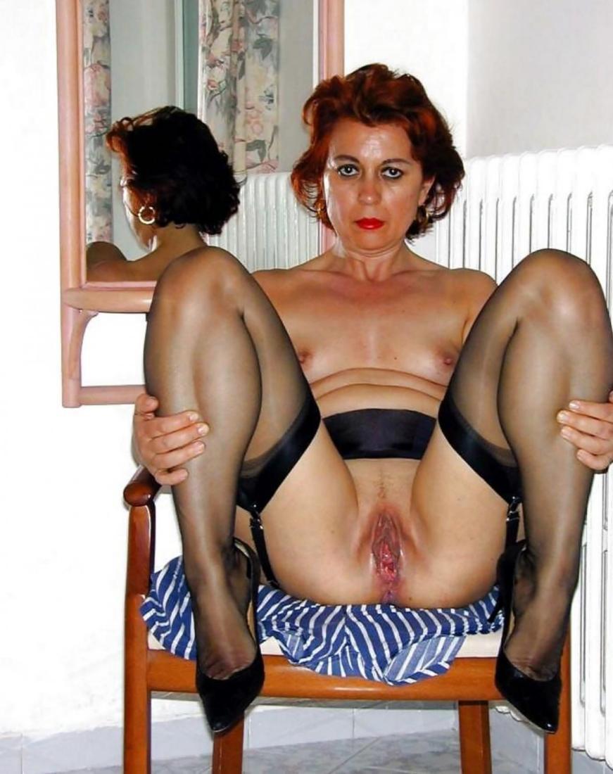 фото голой зрелой женщины сидящей на стуле подняв ноги в черных чулках, видна бритая пизда.
