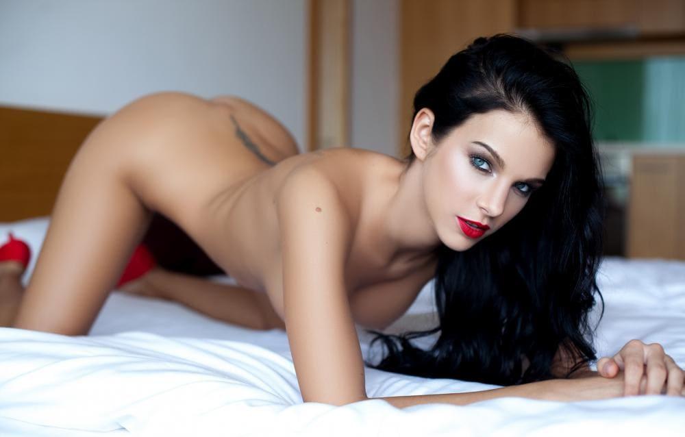 Голые брюнетки раком стоит на кровати в красных туфлях, красная помада на губах