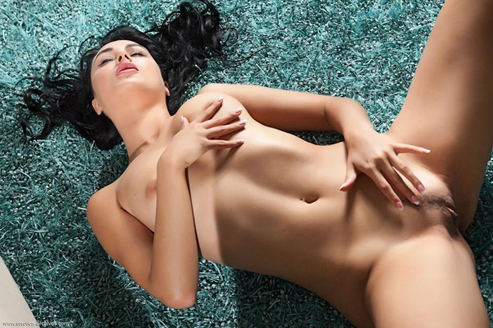Голые пизды брюнеток лежит на спине, левой рукой ласкает свою письку с интимной стрижкой, правой грудь, глаза закрыты, ротик приоткрыт, вид сверху