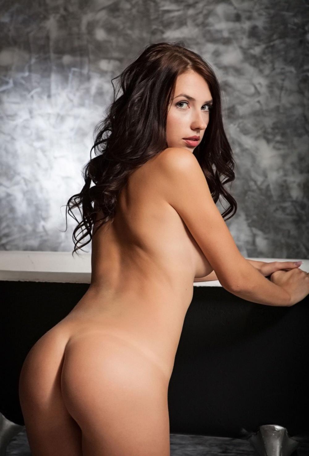 Голая попа брюнетки стоит возле стойки руки на нее положила, вид сзади