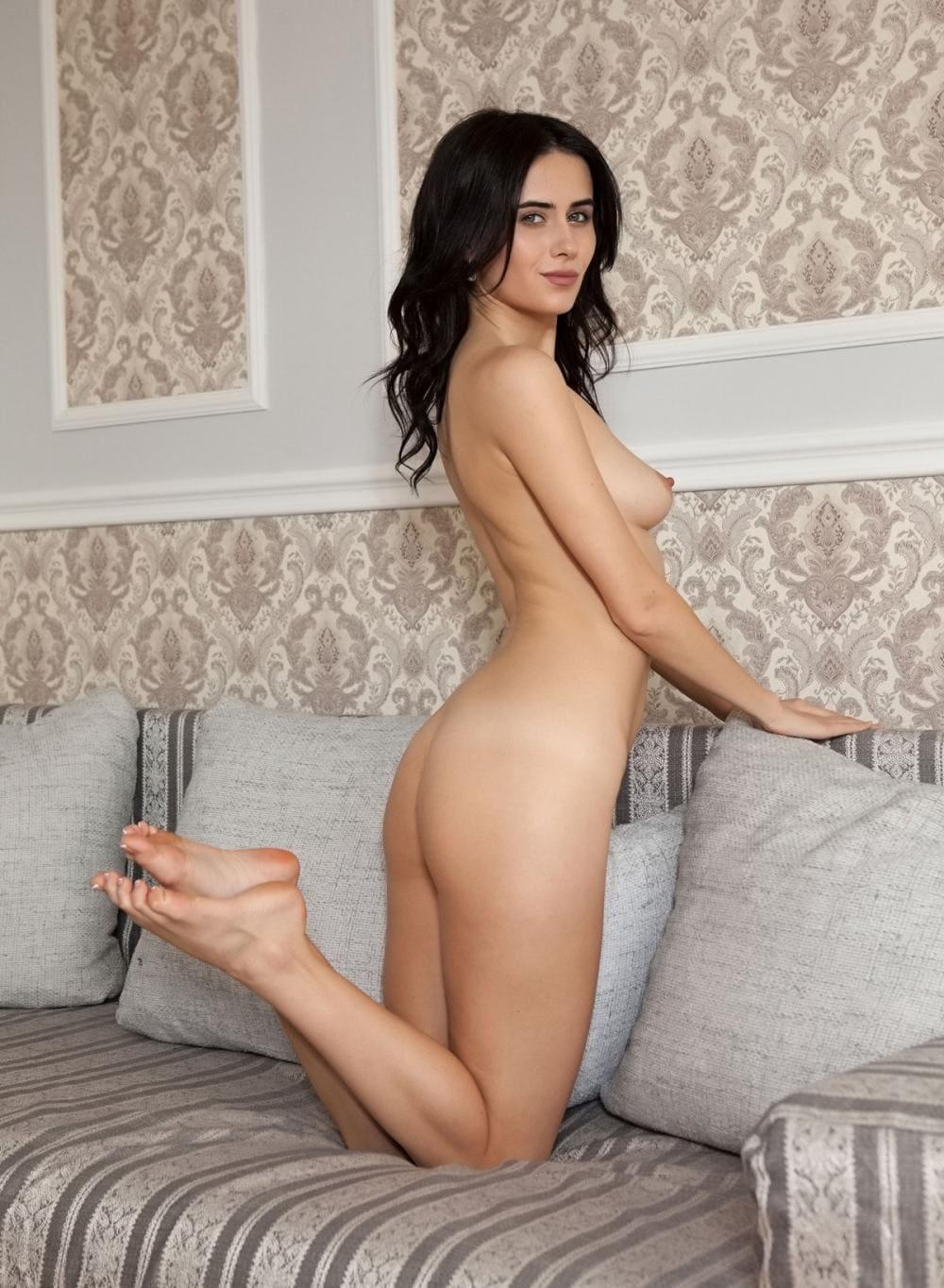 Красивые голые брюнетки стоит возле спинки дивана на коленях и немного подняла стопы, маленькая грудь, симпатичное лицо, улыбается
