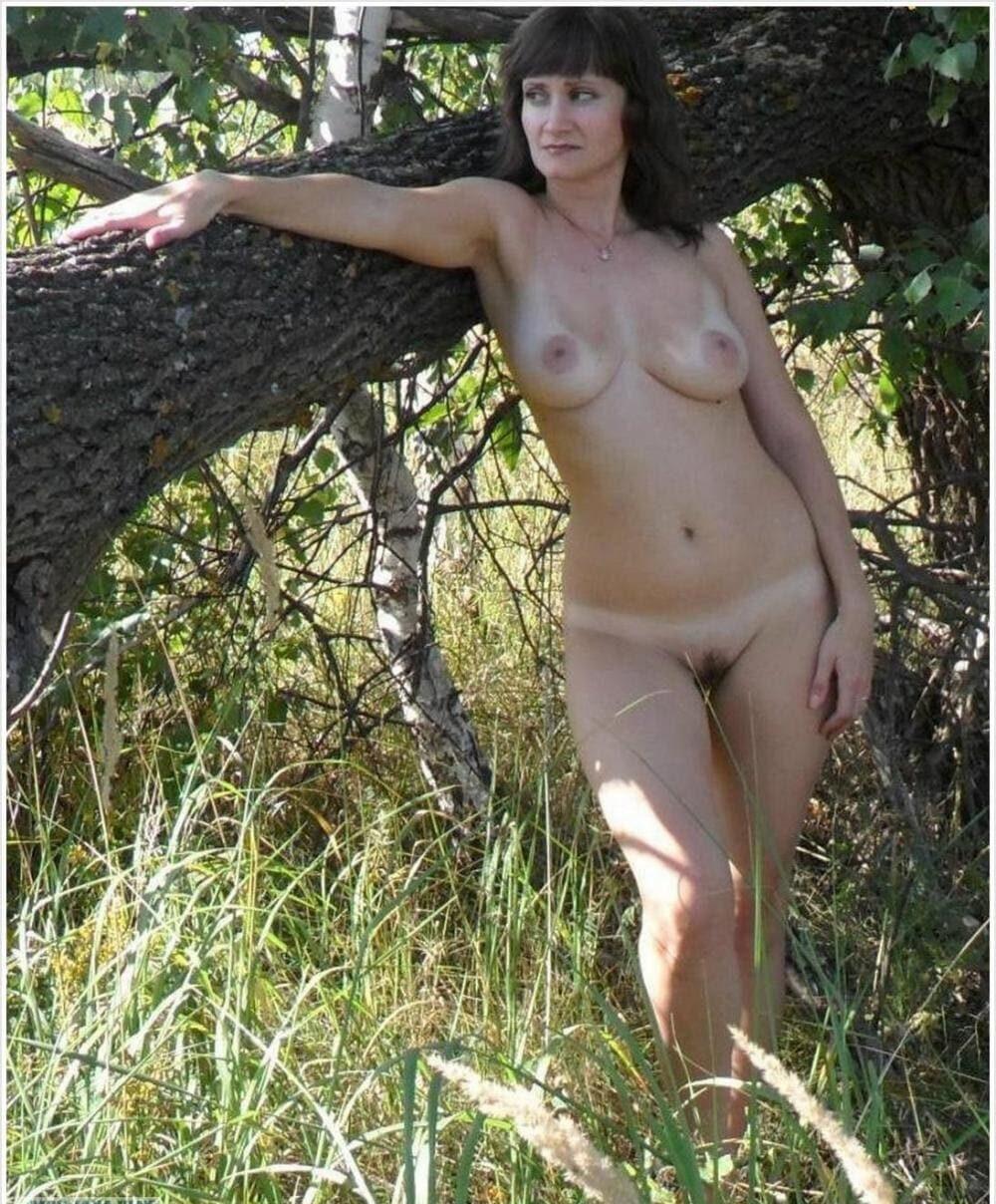 Зрелые женщины на природе красивая, голая с интимной стрижкой, хорошей фигурой стоит у поваленного дерева