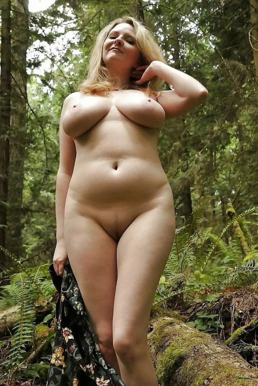 Зрелые женщины на природе красивая блондинка приятных форм стоит в лесу, правую руку подняла и трогает волосы,в левой держит свое платье