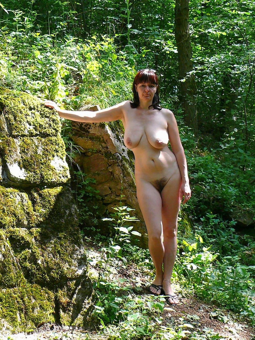 Зрелые волосатые женщины на природе стоит голая возле камня во весь рост, сиськи висят