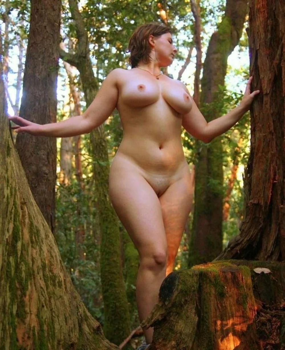 Зрелые женщины на природе шатенка с короткой стрижкой красивой фигурой и сиськами стоит в лесу между деревьев