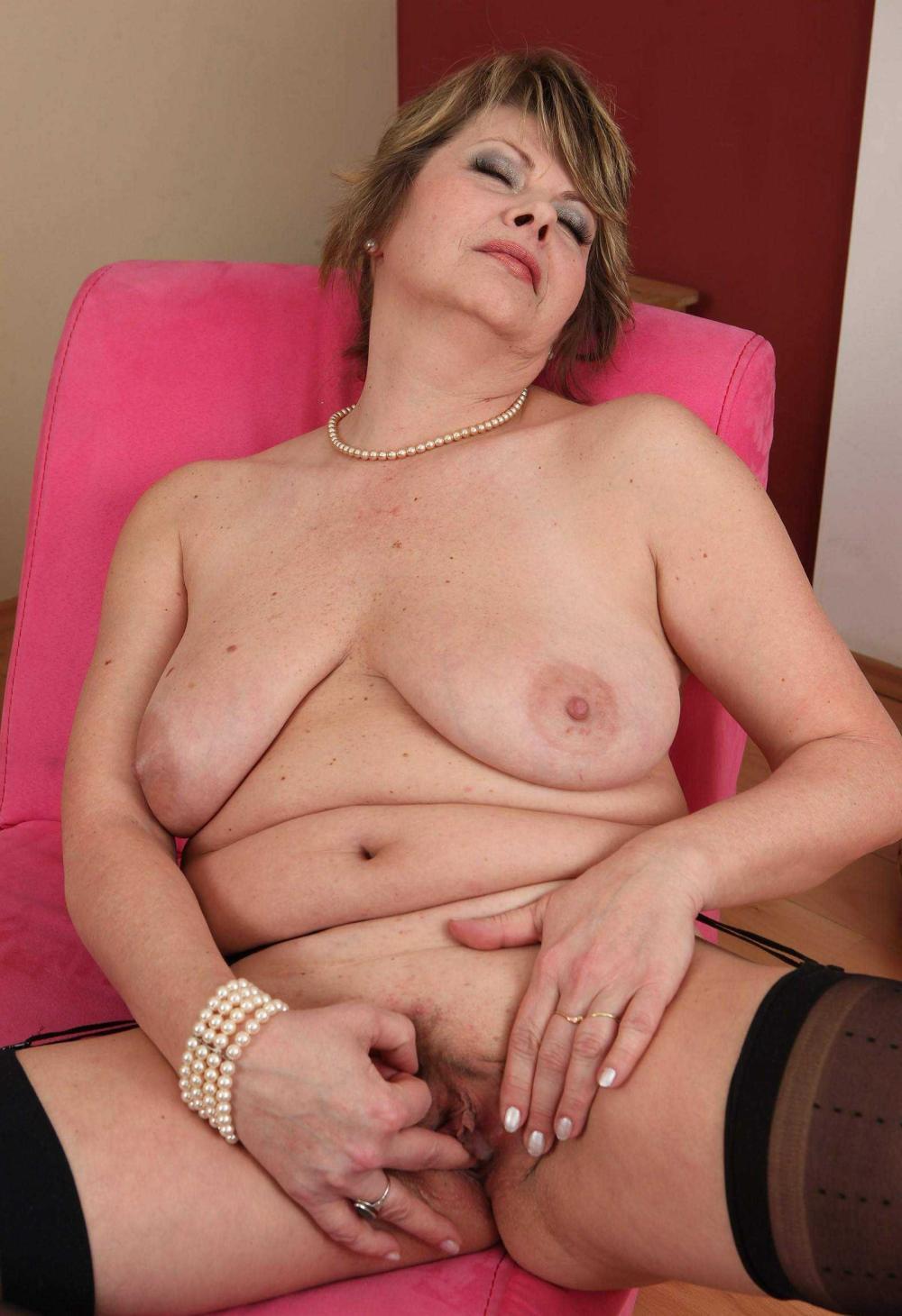 Голые зрелые женщины порно фото сидит в розовом кресле раздвинув ноги в чулках, сиськи висят, правой рукой пальчиками трахает себя, глаза закрыты от удовольствия