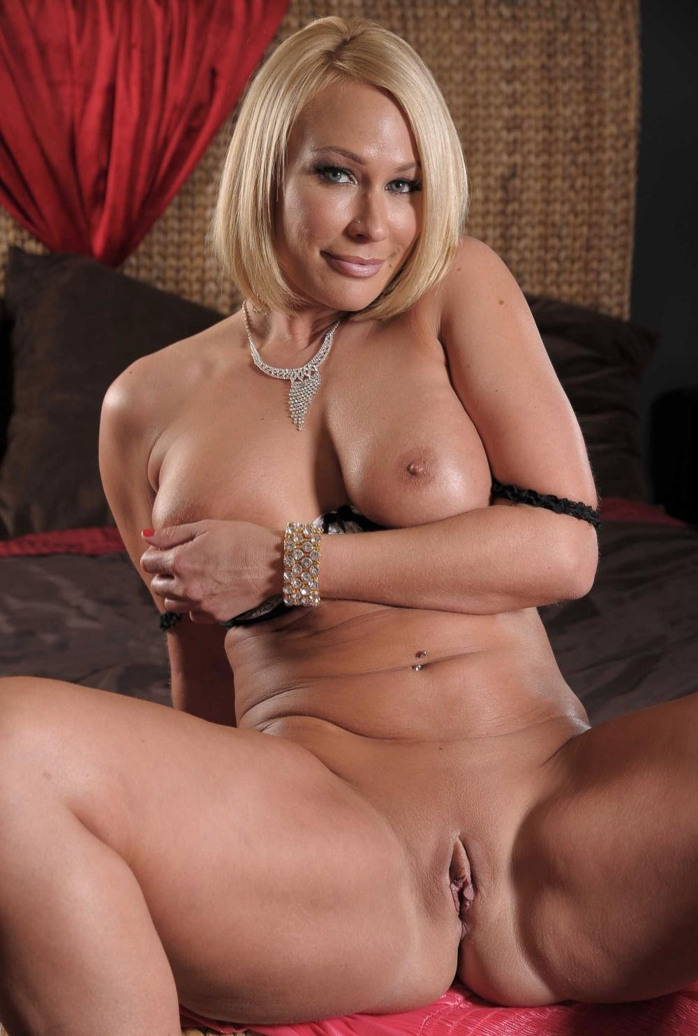 Красивые голые зрелые женщины блондинка сидит правой рукой поддерживает свои шикарные сиськи, в пупке пирсинг, ноги расставила показывая свою аппетитную киску