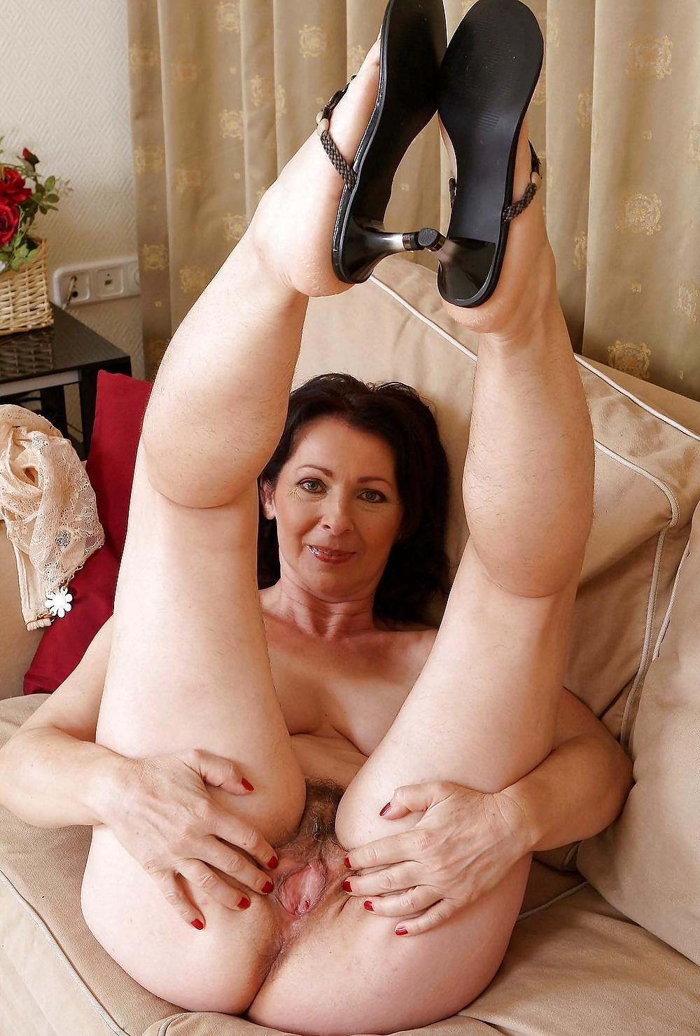 Голые зрелые женщины порно лежит на спине на диване задрав вверх ноги в открытых босоножках на каблуке, руками широко раскрывает свою пизду, смотрит в камеру похотливо улыбается