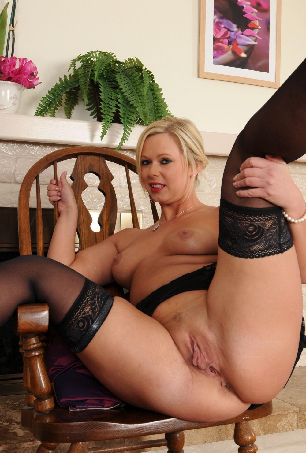 Порно фото голых зрелых женщин блондинка устроилась в деревянном кресле, держится за спинку, задрала ноги в черных чулках подняла их и раздвинула открыв все свои прелести большой возбужденный клитор