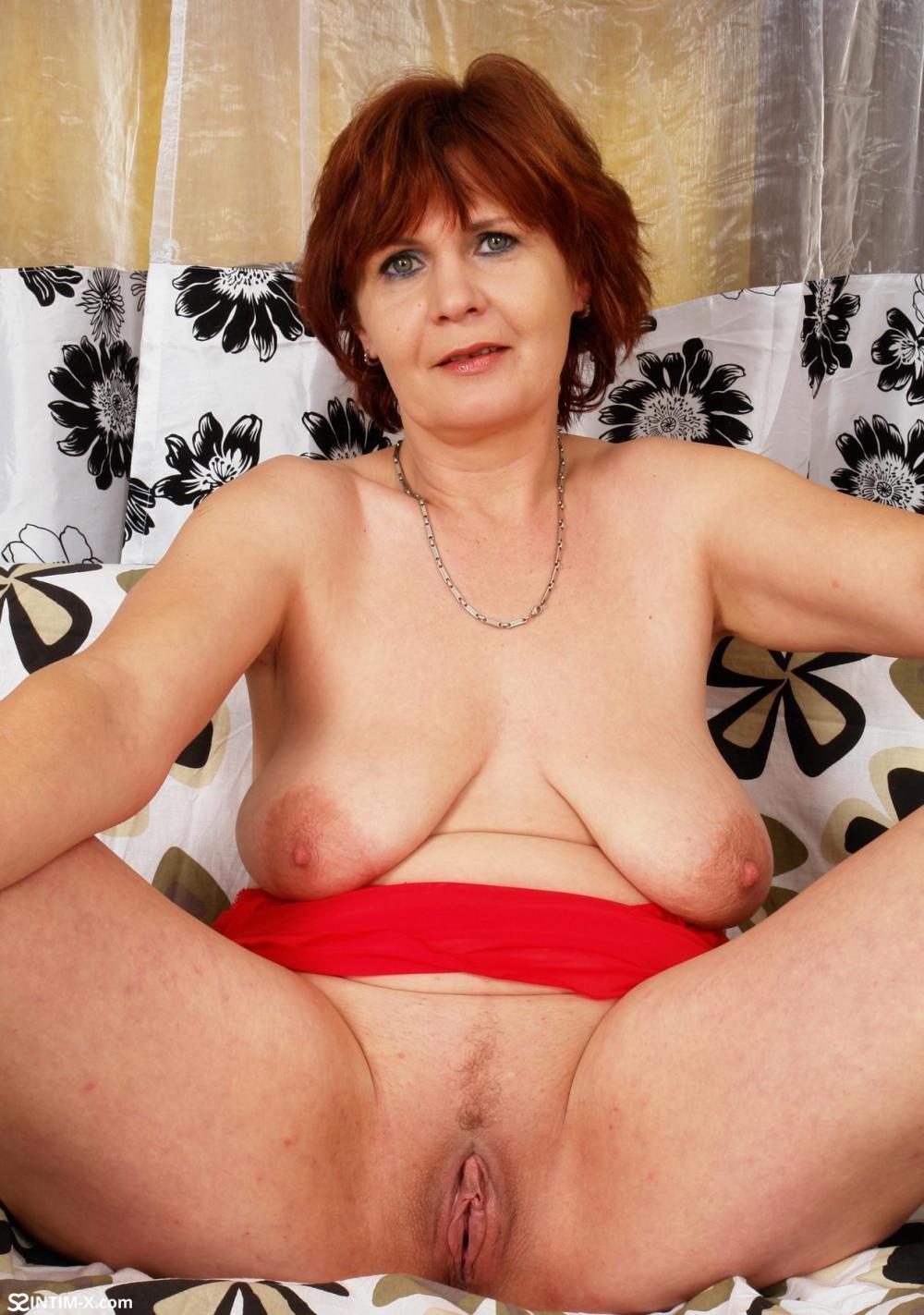 Порно фото голых зрелых женщин брюнетка с короткой стрижкой сидит на попе, сиськи висят, ноги широко раздвинула показывает свою бритую пизду