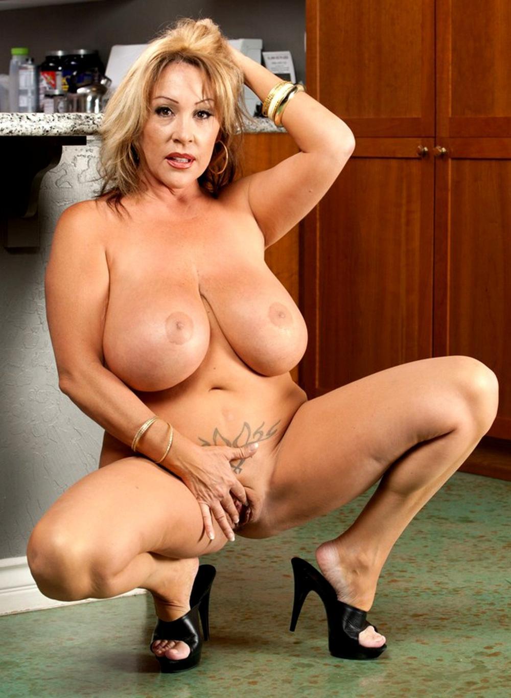 Голая грудь зрелой женщины блондинки, большого размера, сидит на корточках в босоножках на шпильке, левая рука поднята на голову, правой дрочит бритую пизду, на животе сделано тату