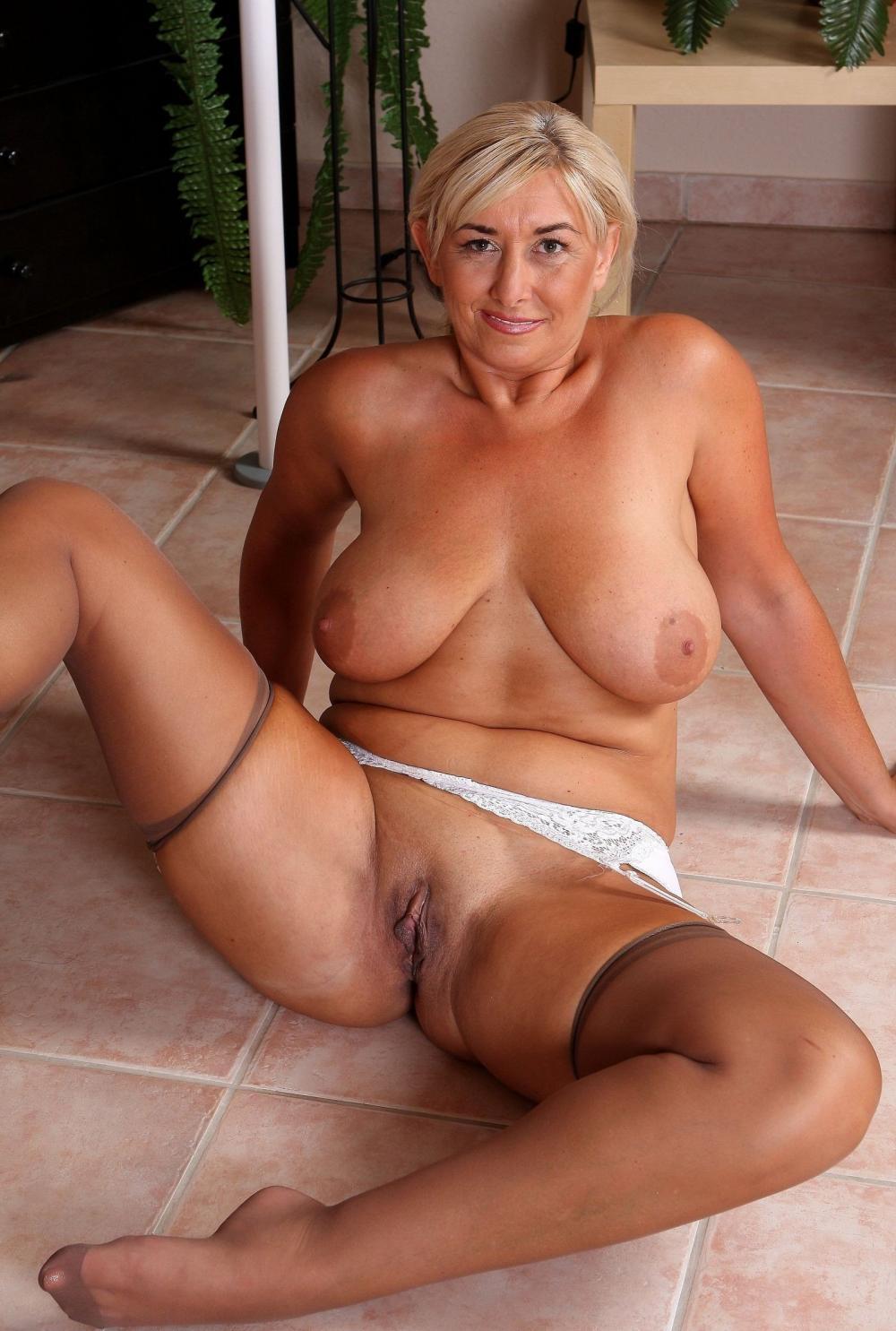 Голые зрелые женщины блондинка сидит на попе на полу в светлых чулках босая, ноги раздвинула, показывает свою бритую пизду