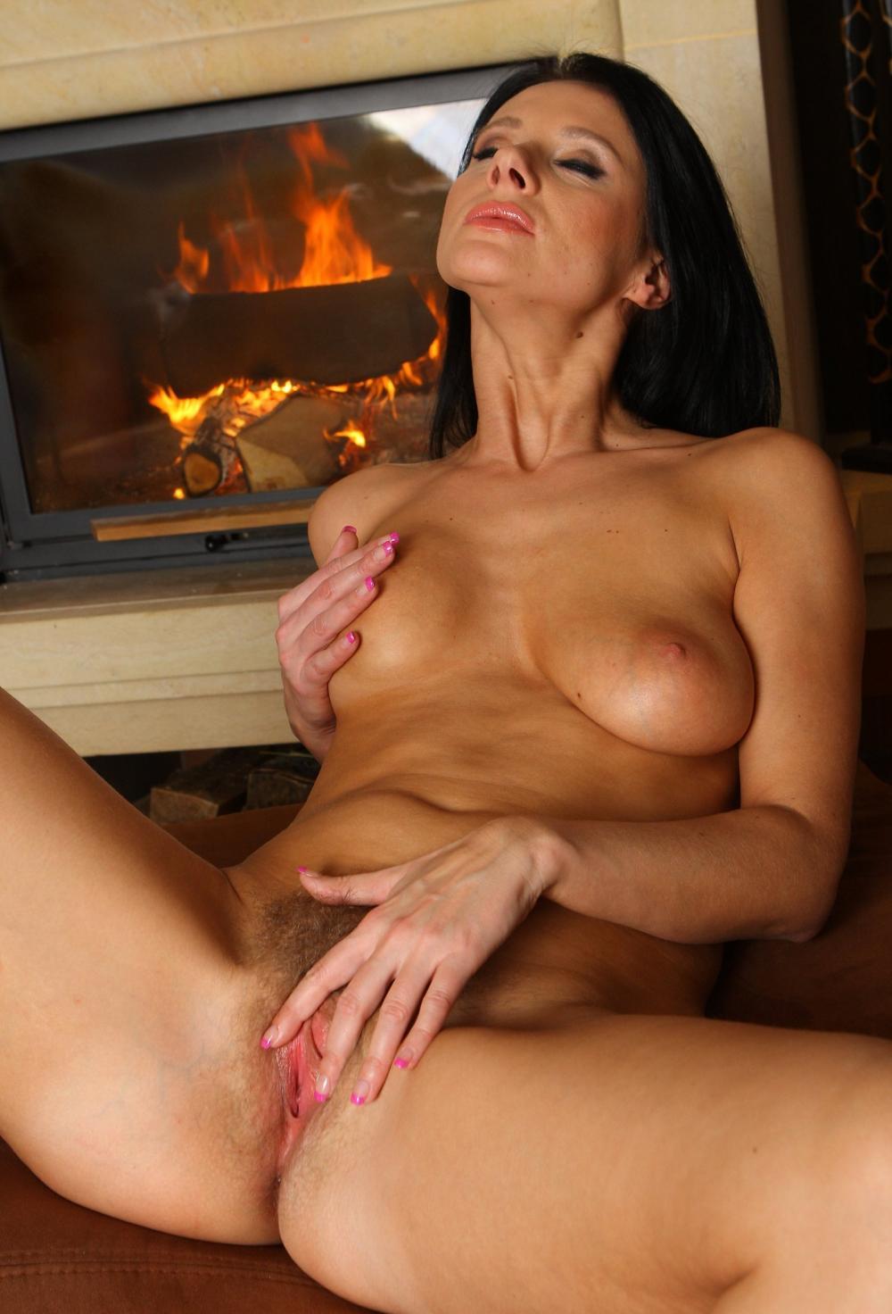 Красивые голые зрелые женщины за 50 сидит возле камина, правой рукой гладит сиську левой раздвигает губки и мастурбирует бритую письку, балдеет
