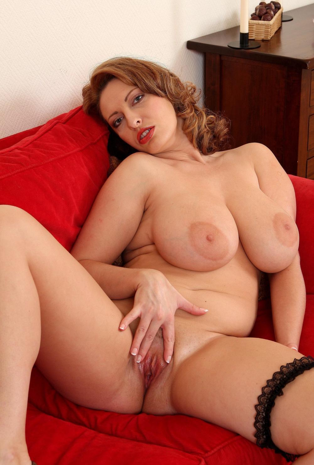 Красивые голые зрелые женщины полусидя на красном диване широко раздвинув ноги, на левой ноге черная подвязка, большая грудь, левой рукой раздвигает половые губы