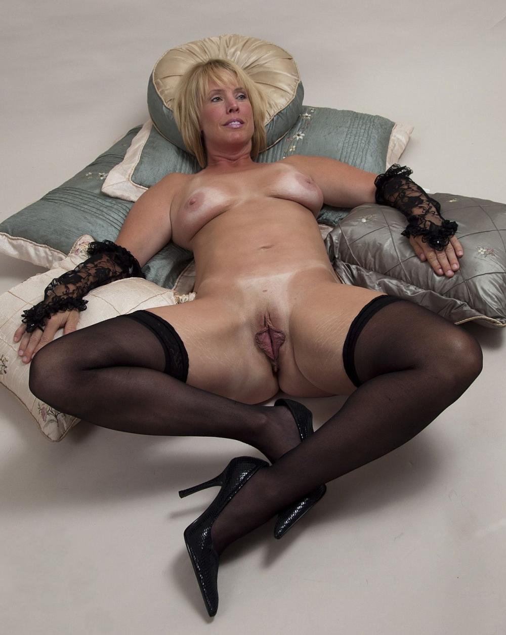 Красивые голые зрелые женщины блондинка с короткой стрижкой лежит на куче подушек, в черных гипюровых митенках, черные чулки, туфли на каблуках, ноги широко раздвинула показала свою красную розочку