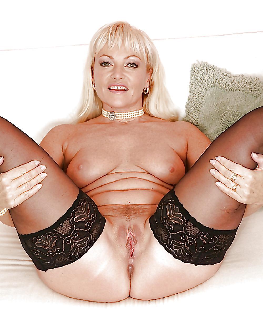 Красивые голые зрелые женщины блондинка в чулках широко раздвинула ноги показывая свою пизду, маленькая висячая грудь, на шее юусы короткие, улыбается