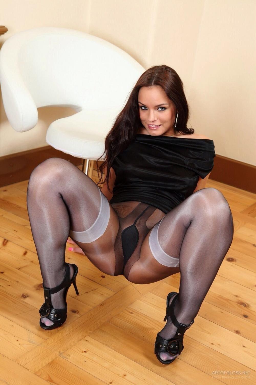 Девушки в чулках и блестящих колготках, черных босоножках на каблуке, полу присев оперлась назад руками, раздвинула ноги