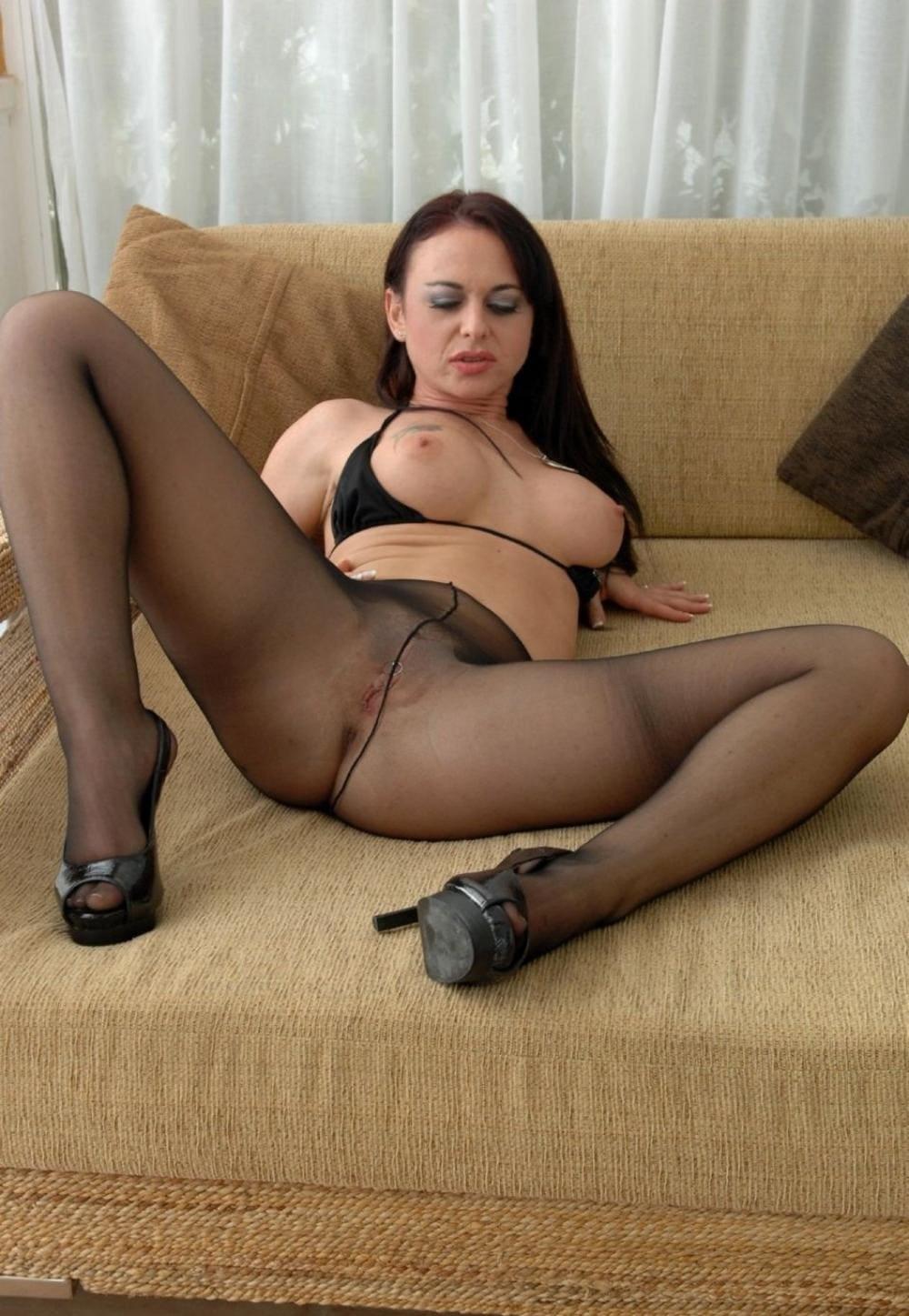 Девушки в черных колготках лежит на диване брюнетка широко расставив ноги в туфлях на высоком каблуке