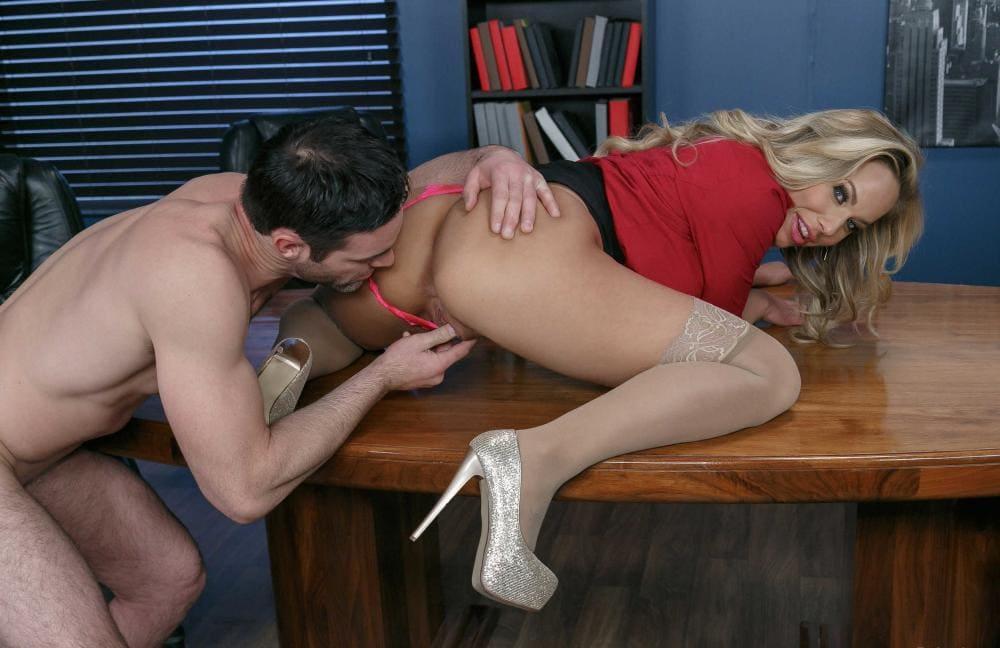 Секс на столе в офисе с блондинкой в чулках лежит на животе, мужчина стягивает трусики и мастурбирует ей пизду