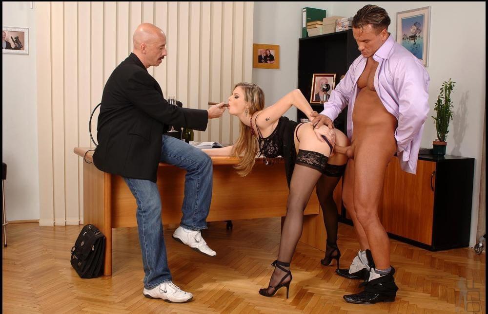 Порно секс в офисе два мужчины и телка стоит раком у стола в чулках. один ебет ее сзади, а второй дает пососать сигару