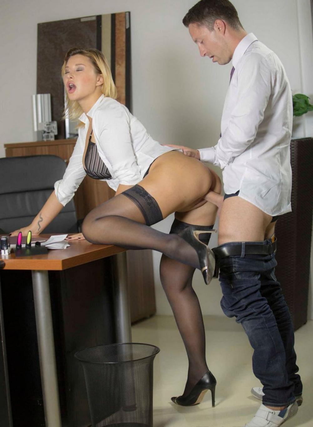 Страстный секс в офисе с блондинкой стоит в чулках и туфлях на каблуке, белой расстегнутой блузе, левую ногу согнула и поставила коленом на стол коллега по работе в белой рубашке приспустив штаны ебет ее сзади