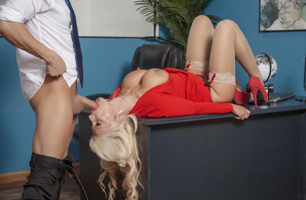 Секс на столе в офисе блондинка в красном платье в чулках, красных туфлях на каблуках сосет хуй лежа на столе на спине, голова запрокинута и свисает