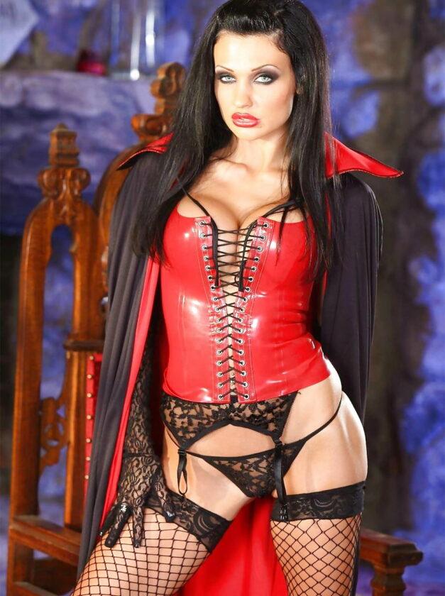 Аллета Оушен стоит в красном корсете черных чулках на поясе