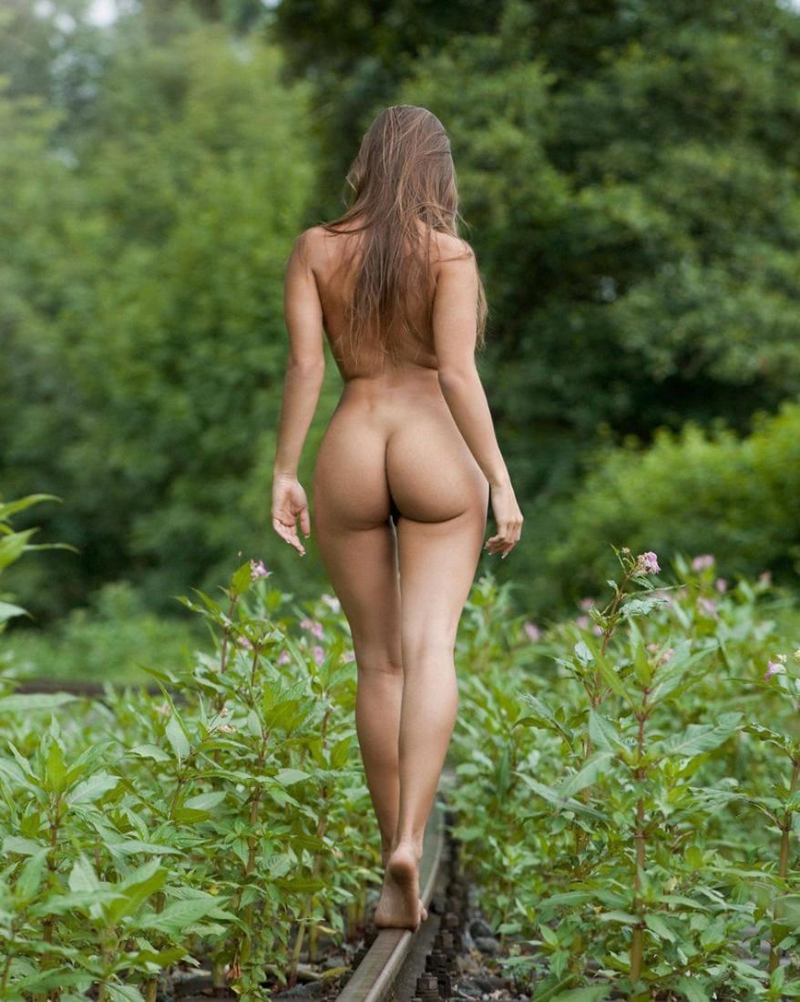 Обнаженная девушка с голой попкой идет босыми ногами по релсе лежащей в густом зеленом лесу. Вид со спины.