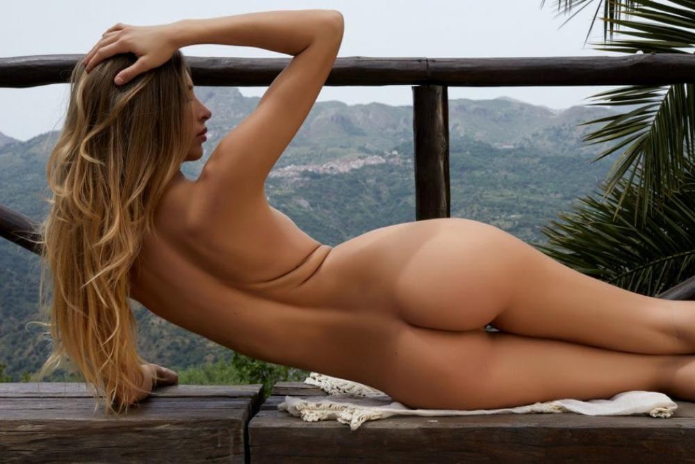 голая попа девушки фото блондинка с длинным распущенным волосом лежит на боку на деревянной скамейке на фоне гор