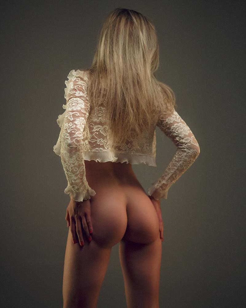 голая попа девушки блондинки с длинным распущенным волосом в светлой гипюровой кофточке, руки положила на бедра