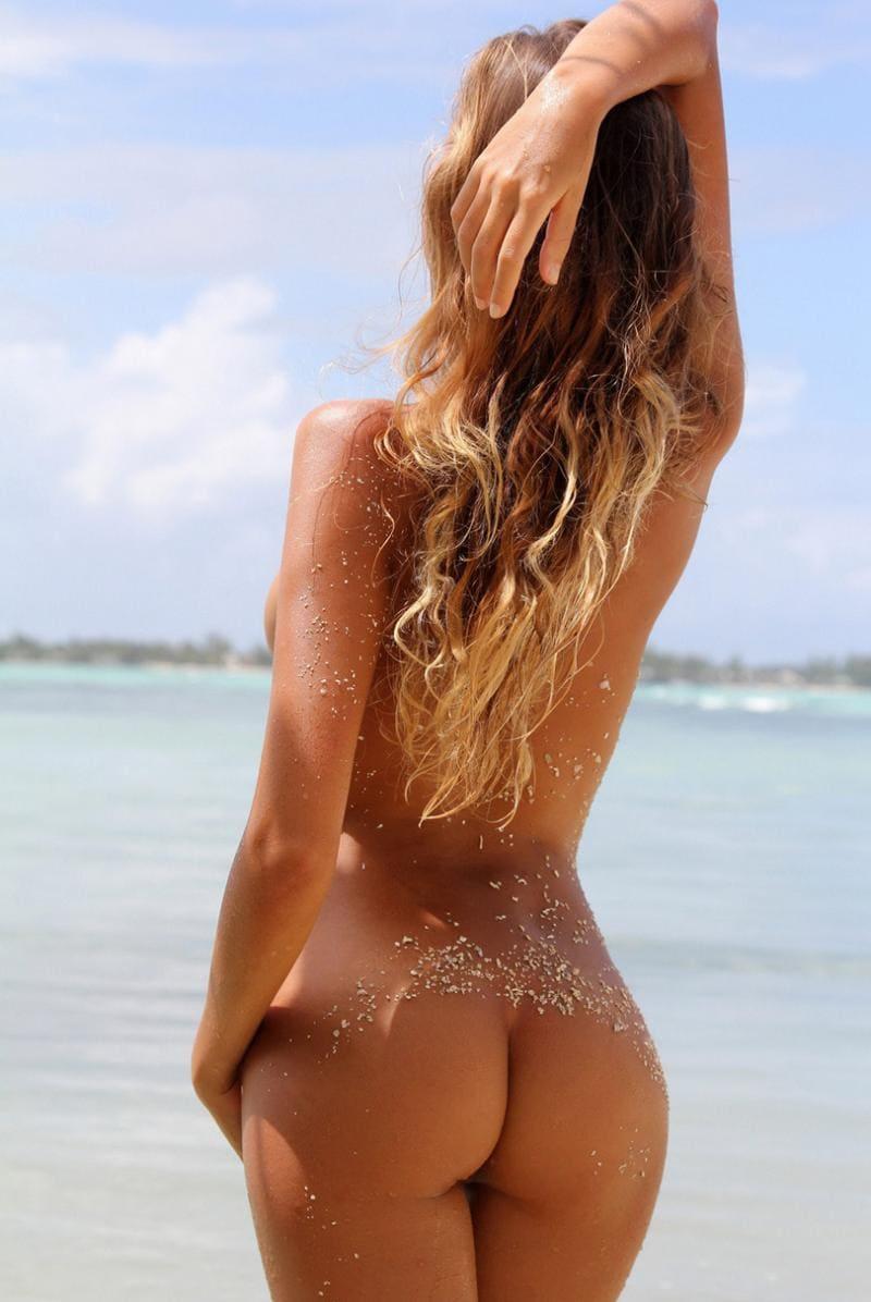 красивые голые попы девушек стоит на берегу водоема руку подняла на голову, волосы распущены, на попе прилип песок