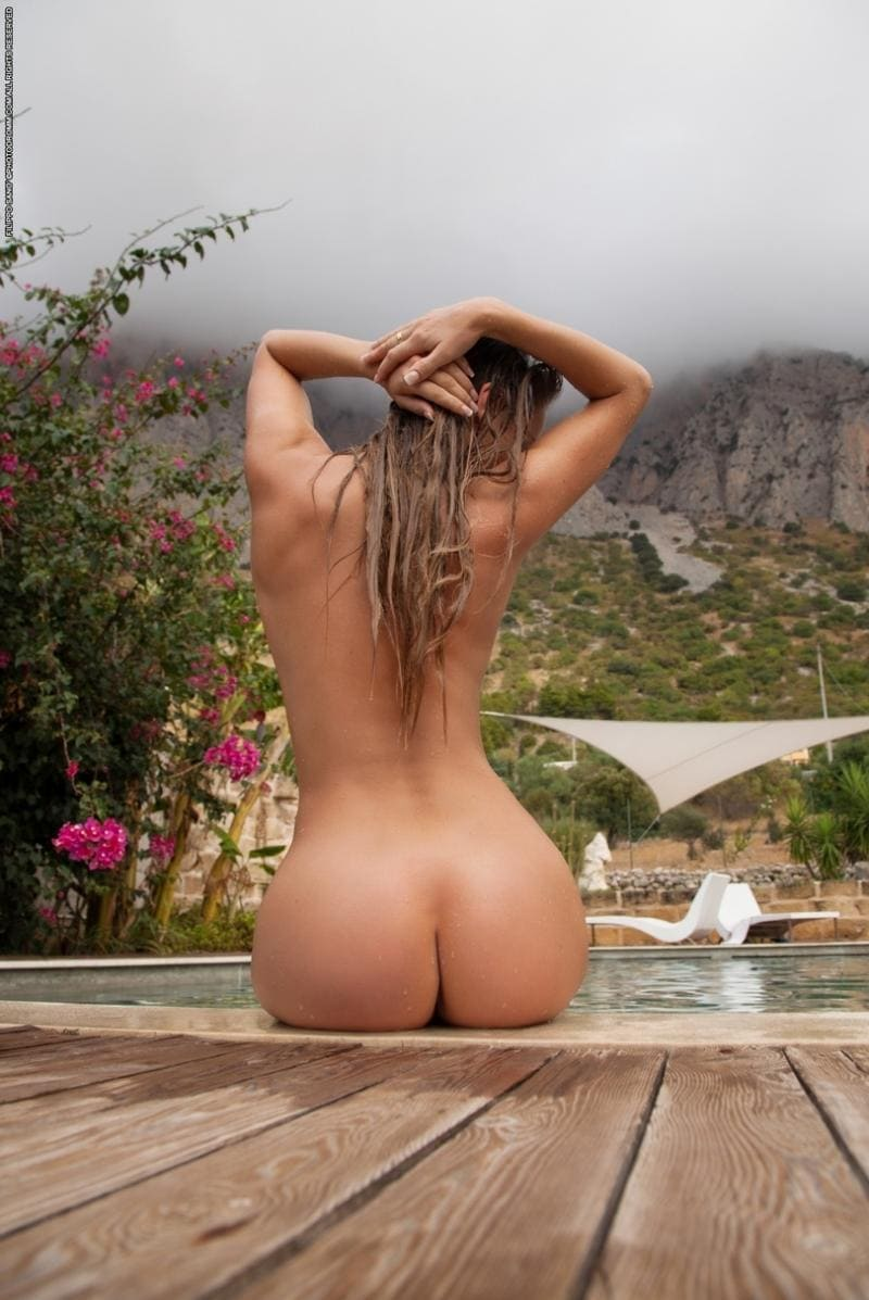 голая попа девушки блондинки с длинным мокрым волосом сидящей возле бассейна
