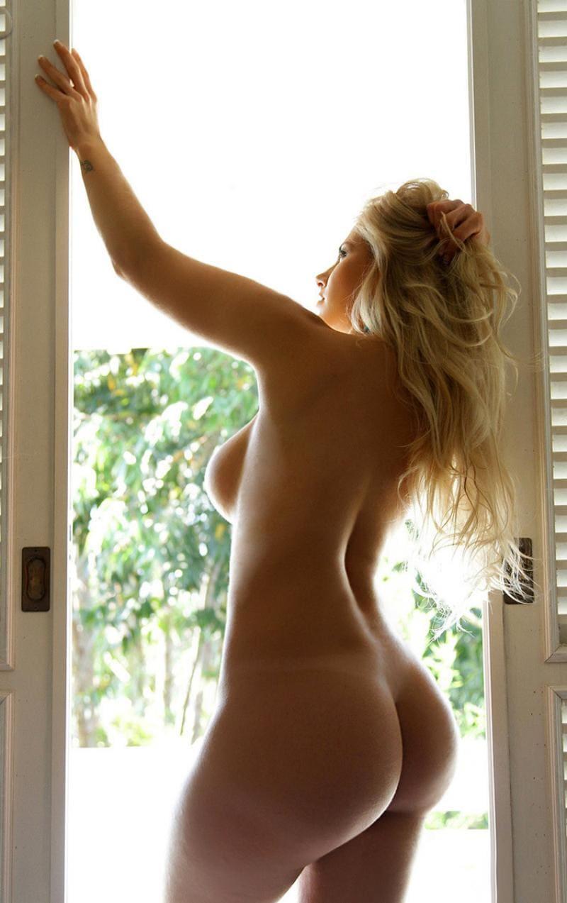 голая попа девушки блондинки,с хорошим размером сисек, стоящей в дверном проеме