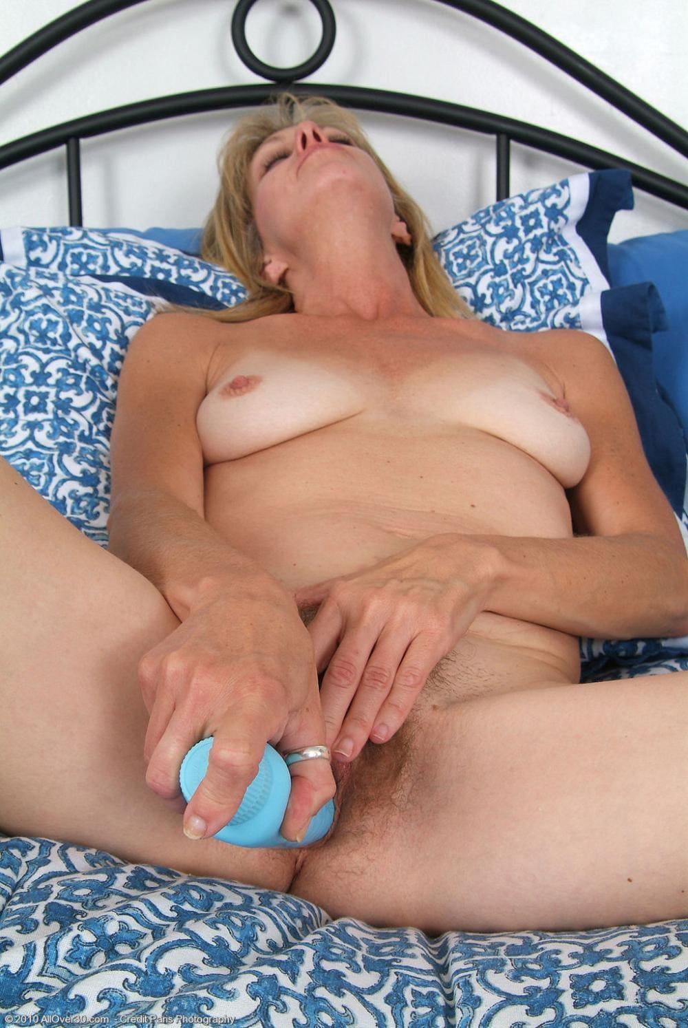 зрелые волосатые мастурбируют вибратором лежа на кровати раздвинув широко ноги