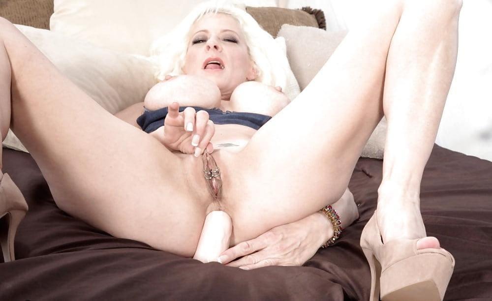 зрелые женщины мастурбируют анал фаллоимитатором блондинка с большими сиськами на кровати лежит на спине широко раздвинув ноги в босоножках на платформе и высоком каблуке, в пизде пирсинг, на лице удовольствие
