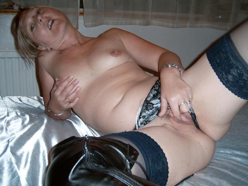 зрелая в чулках мастурбирует пальчиками лежа на кровати широко раздвинув ноги