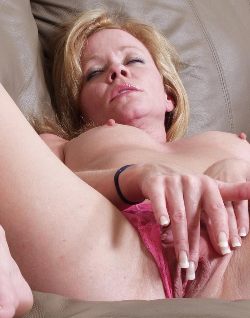красивая зрелая мастурбирует лежа на спине раздвинув ноги, отодвинув трусики, и пальчиками с французским маникюром ласкает свою киску, на лице блаженство