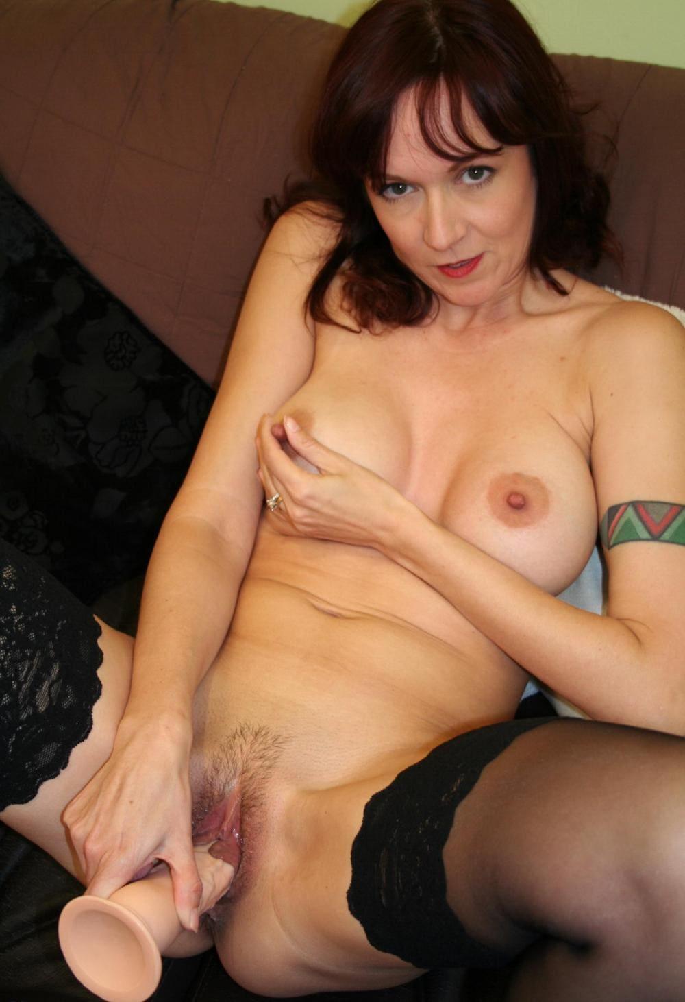 зрелая в чулках мастурбирует полусидя на диване широко раздвинув ноги ласкает левой рукой, с татуировкой на предплечье в виде браслета, сиськи, а правой держит фаллоимитатор и трахает себя, интимная стрижка на пизде