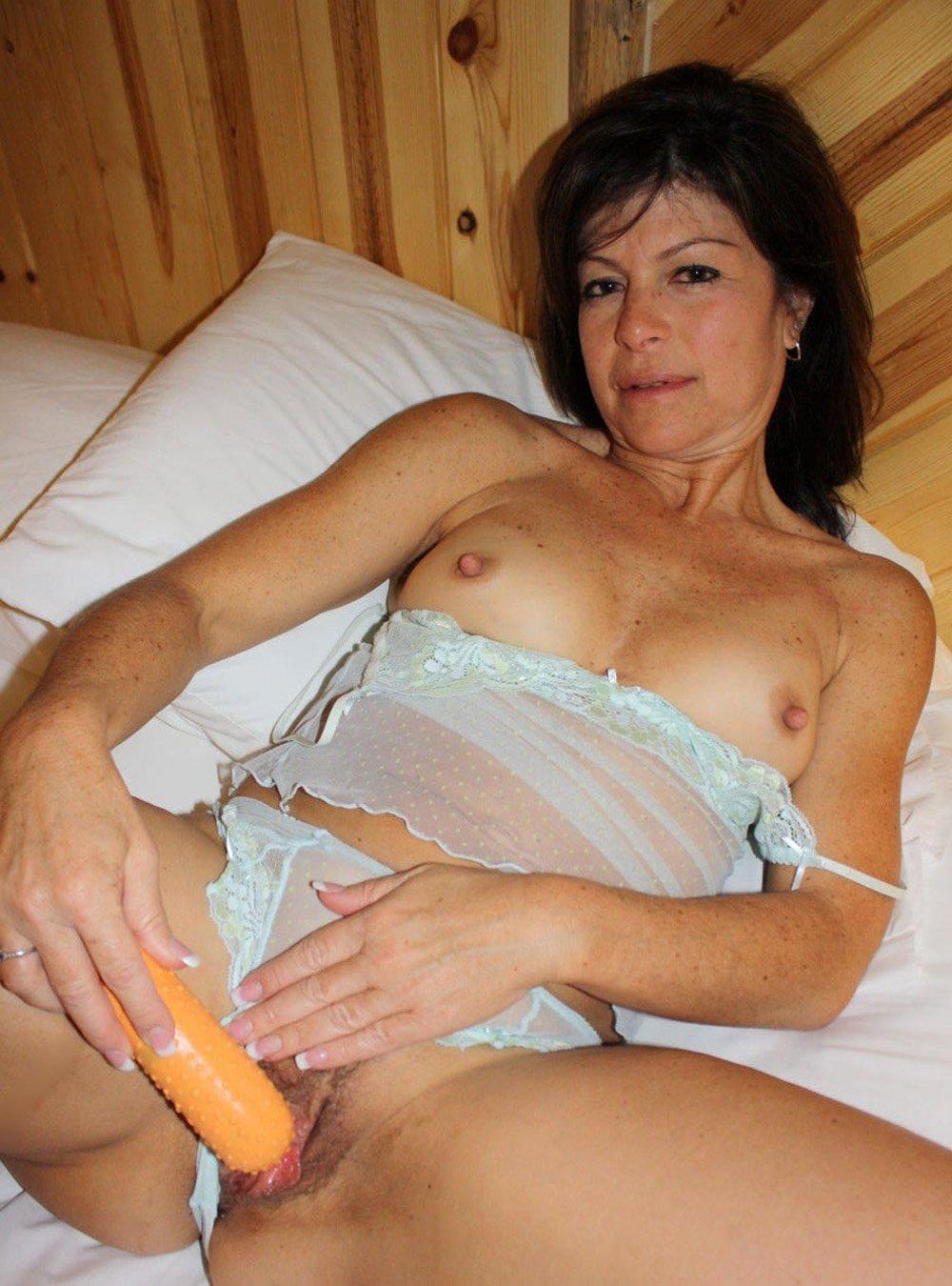 зрелые женщины мастурбируют красивая брюнетка лежит на спине на кровати в светлом прозрачном нижнем белье отодвинула немного в сторону трусики и фаллоимитатором мастурбирует свою киску