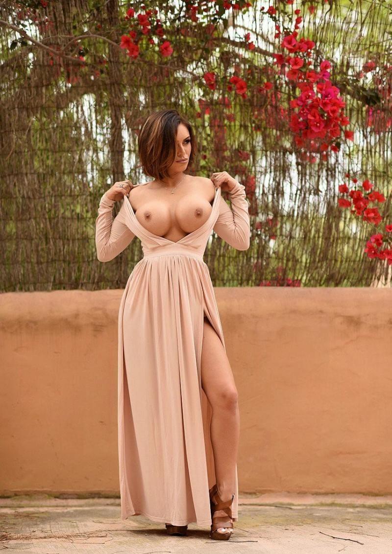 девушка шатенка с короткой стрижкой в длинном светлом платье с большим разрезом стоит, снимает плечики показывая большие голые сиськи