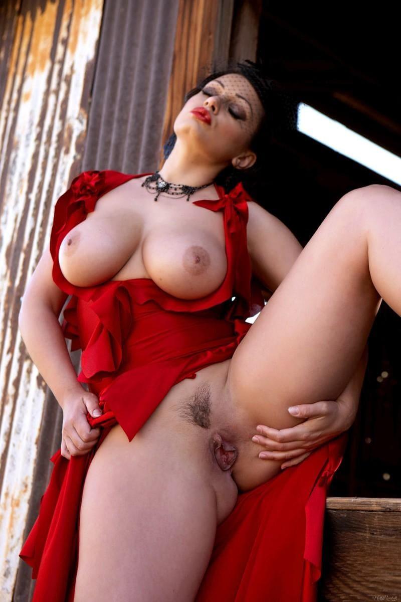 порно фото брюнетки вывалила большие сиськи с красного платья, юбку задрала, подняла вверх левую ногу и показала свою пизду с интимной стрижкой во всей красе