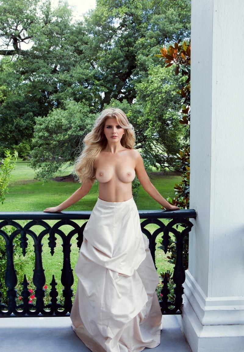 красивые сиськи в платье блондинки с длинным распущенным волосом стоящей на веранде в саду