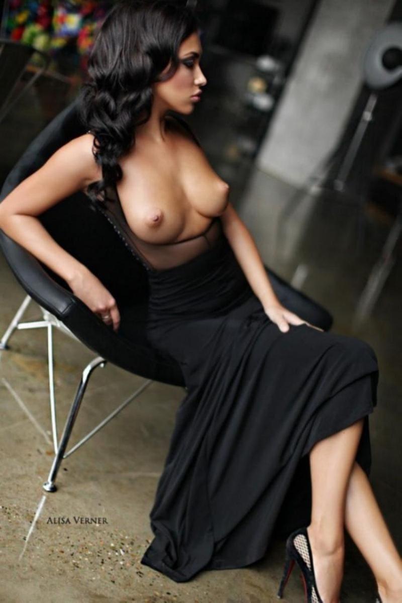 сиськи в платье красивой брюнетки сидящей на стуле в длинном расстегнутом черном платье
