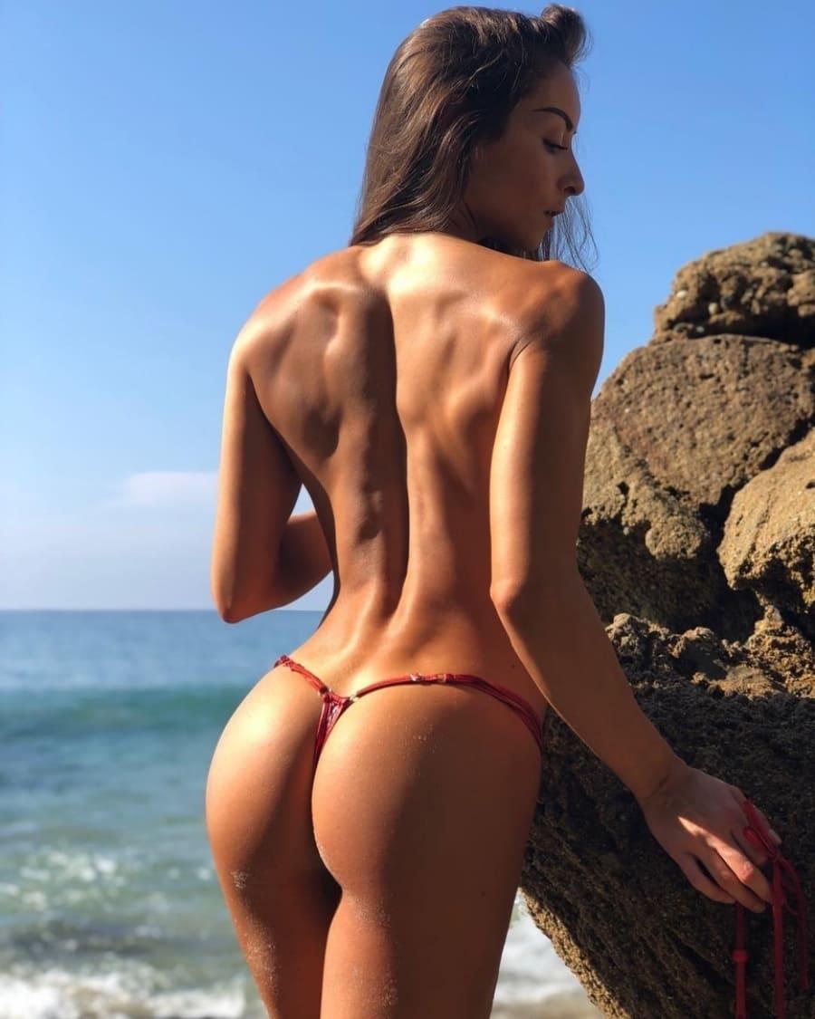 фото девушек в стрингах голая на пляже у камня на берегу океана стоит