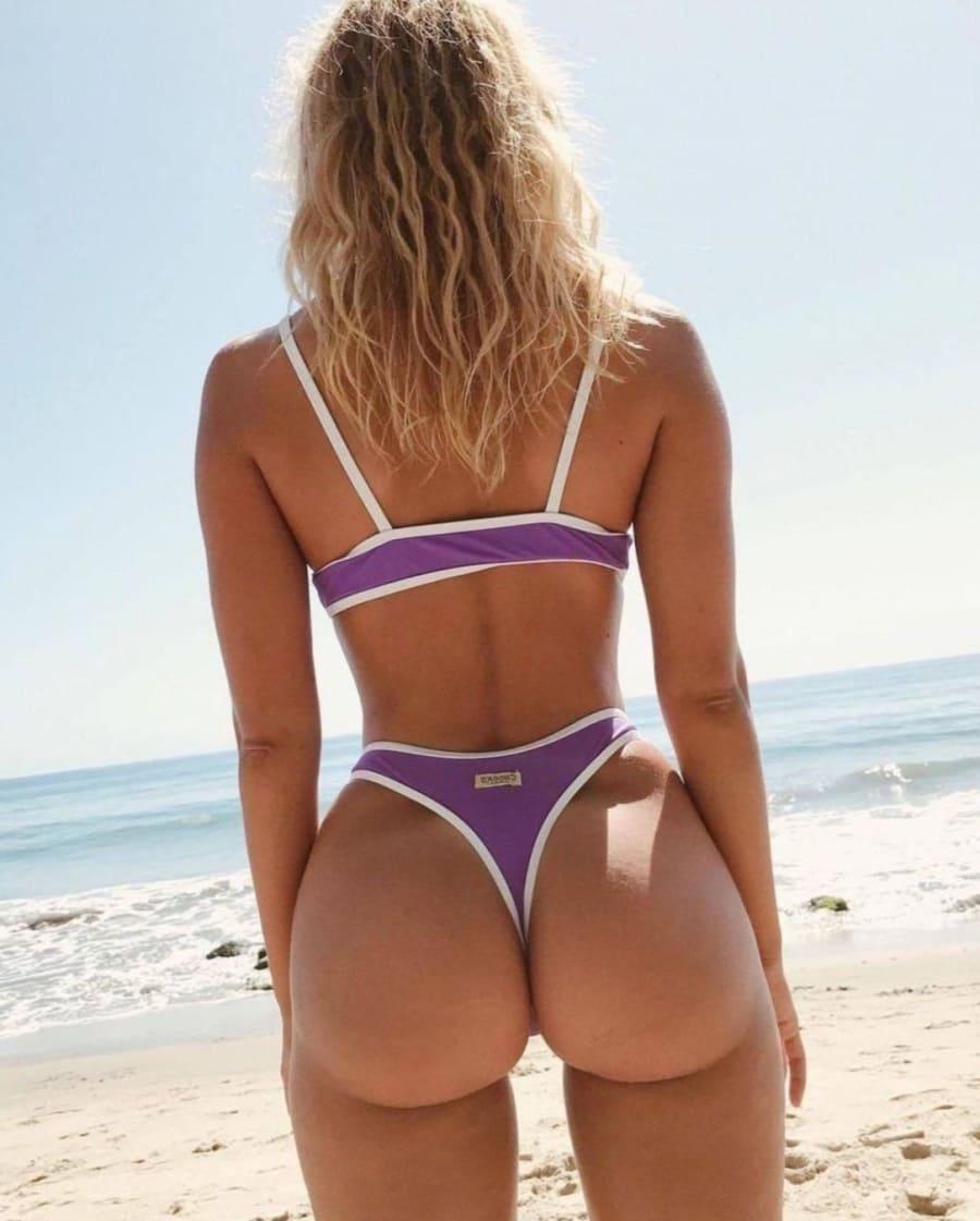 фото девушек в стрингах блондинка в фиолетовом купальнике стоит на берегу моря, красивая попа